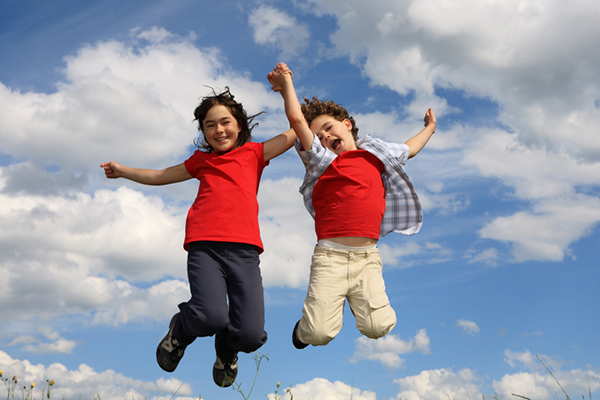 Two kids jumping in the air